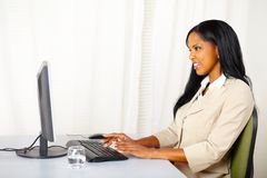 Friendly businesswoman working on computer Royalty Free Stock Photos