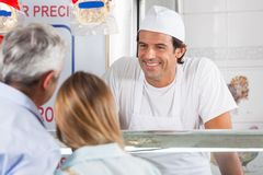 Friendly Butcher Smiling At Customers Stock Photography