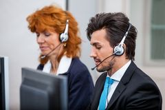 Friendly callcenter agent operator with headset telephone Stock Photos