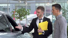 Friendly car dealer helping his male customer choosing automobile to buy. Young men getting advice on buying new car from dealership salesman. Transportation royalty free stock image