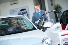 Friendly car dealer showing new car to customer Royalty Free Stock Images