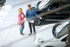 Friendly car dealer showing young women new car Stock Photography