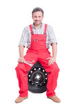 Friendly car mechanic resting on wheel Royalty Free Stock Images