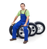 Friendly car mechanic sitting on tires Stock Photography
