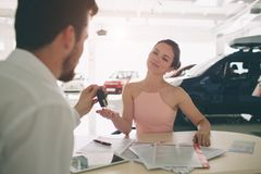 Friendly car salesman talking to a young woman and showing a new car inside showroom Signing of contract. Friendly car salesman talking to a young women and stock photography