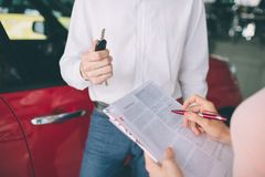 Friendly car salesman talking to a young woman and showing a new car inside showroom Signing of contract. stock photo