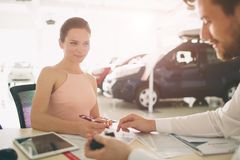 Friendly car salesman talking to a young woman and showing a new car inside showroom Signing of contract. Friendly car salesman talking to a young women and stock photo