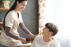Senior woman sick with alzheimer. Friendly caregiver giving cup of tea senior women sick with alzheimer during visit at home Royalty Free Stock Photography