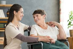 Friendly caregiver woman hugging senior. Friendly caregiver women hugging smiling senior women in wheelchair during visit at home Stock Photos
