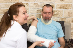 Friendly carer. A nurse smiles while examining an injured man Stock Photo