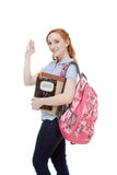 Friendly Caucasian college student with backpack. Education series - Friendly Caucasian female high school student with backpack and composition book greeting Royalty Free Stock Photo