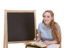 Friendly Caucasian college student by blackboard. High school or college Caucasian redhead woman student sitting by the desk. Blank blackboard with copyspace is Royalty Free Stock Image