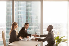 Friendly caucasian employers and african-american applicant hand. Friendly caucasian employers and confident african-american applicant handshaking during job Royalty Free Stock Photo