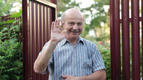 Friendly caucasian old man waving hi or farewell, isolated outdoors background with green trees and fence stock video