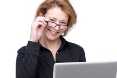 Friendly Caucasian Woman and Laptop. Caucasian business woman holding her laptop and looking at the camera. She is smiling and holding her glasses. Isolated stock photography