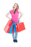 Friendly cheerful girl standing with mouth open and holding bags Stock Image