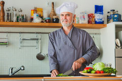Friendly chef preparing vegetables in his kitchen Stock Images
