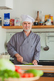 Friendly chef preparing vegetables in his kitchen Royalty Free Stock Images