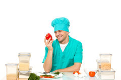 Friendly chef preparing vegetables in his kitchen. pepper loves Stock Image