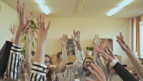 Friendly classmates sit at a desk and raise their hands together. Russian school. College Students Teamwork Stacking stock video