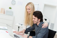 Friendly co-workers at the office. Friendly and happy male and female co-workers working at the office on a laptop Stock Photo