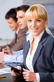 Friendly colleague. Portrait of friendly smiling woman on the background of her colleagues Stock Photography