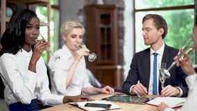 Friendly colleagues at a business meeting with a champagne. Clinking Glasses With Champagne At The Business Meeting. Smiling Colleagues Hold A Glass Of Champagne stock video footage