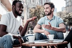 Friendly colleagues discussing their work outdoors. We love what we do. Happy coworkers gesturing and smiling cheerfully while enjoying a pleasant conversation Royalty Free Stock Photo