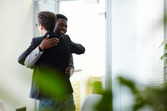 Friendly colleagues. Happy colleagues greeting one another by embrace stock image