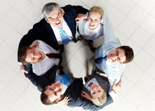 Friendly company. Above view of several happy business partners looking at camera while embracing each other Royalty Free Stock Photos