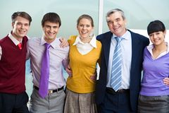 Friendly company. Portrait of happy colleagues embracing and looking at camera with smiles Royalty Free Stock Photography