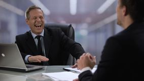 Friendly company boss and male worker laughing, giving high five at meeting. Stock footage stock footage