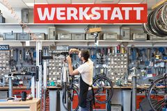 Friendly and competent bicycle mechanic in a workshop repairs a. Bike - building Stock Images