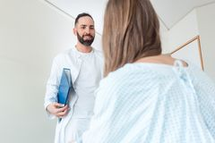 Doctor seeing patient in hospital. Friendly and competent Doctor seeing patient in hospital royalty free stock images