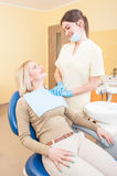 Friendly and confident female dentist assistant. Conforting a patient Royalty Free Stock Photos