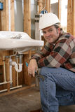 Friendly Construction Plumber. A friendly plumber installing bathroom fixtures on a construction site Royalty Free Stock Photography