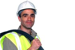 Friendly construction worker. With a cable on his shoulder looking into the camera Royalty Free Stock Images