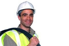 Friendly construction worker. With a cable on his shoulder looking into the camera Stock Image