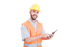 Friendly construction worker using tablet. Friendly and modern construction worker or builder using tablet royalty free stock photography