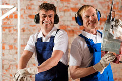 Friendly construction workers with air hammer Royalty Free Stock Images