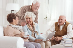 Friendly conversation of elderly neighbors. Drinking tee, and using laptop Royalty Free Stock Images
