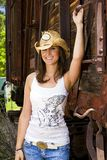 Friendly, country girl. A beautiful country girl with a friendly smile wearing denim blue jeans and a cowboy hat Royalty Free Stock Photo
