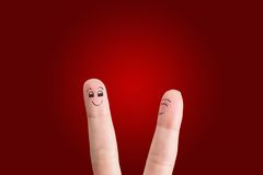 Friendly couple. Painted at fingers isolated on red background stock image