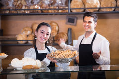 Friendly couple selling pastry and loaves. Friendly couple selling fresh pastry and loaves in bread section royalty free stock photo