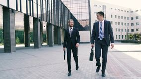 Friendly coworkers walking on the street near office building. Friendly coworkers in beautiful suits walking on the street near office building. They are going stock video