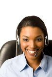 Friendly Customer Service. Close-up of a happy, friendly young african american woman wearing a headset Royalty Free Stock Photo