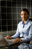 Friendly Customer Service. Waist-up portrait of a happy, friendly young african american woman wearing a headset and typing on a laptop Stock Photography