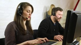 Friendly customer service call centre staff chatting to customers on headsets stock video footage