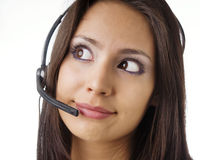 Friendly customer service representative. Attractive friendly customer service representative at work answering phone calls using a headset Royalty Free Stock Images