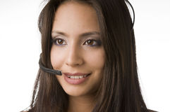 Friendly customer service representative. Attractive friendly customer service representative at work answering phone calls using a headset Royalty Free Stock Image